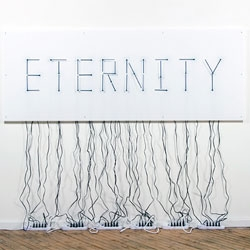 Alicia Eggert and Mike Fleming use clock hands to create the words Eternity every 12 hours.