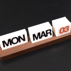 "Solid Walnut Based perpetual calendar, features 1/16"" white acrylic tabs with black and orange lettering in helvetica font. Each set comes complete with full set of days, months and dates."