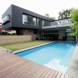 house, by ong & ong, most attention-grabbing detail is the dark grey metal cladding on the external facade, complemented by teak strips used liberally throughout the whole house.