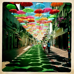 In Águeda, a small Portuguese town, some streets are decorated with colorful umbrellas that seem to magically float in mid-air, sheltering people on the streets below from the hot summer sun!