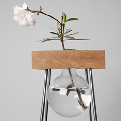 Flower - A table that combines the warmth of the wood with the purity of glass, to expose nature in its beauty, by designers Adam & Samuel Cigler.