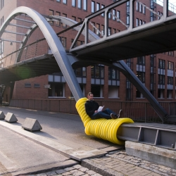'Street Furniture,' a series of guerilla public seating areas created by wrapping yellow drainage pipes around existing urban infrastructure.