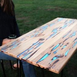 Glow powder mixed with clear casting resin fills the naturally formed voids in this Pecky Cypress hardwood, creating a unique and stunning table. Charging in sunlight, it emits a cool blue glow when in partial or complete darkness.