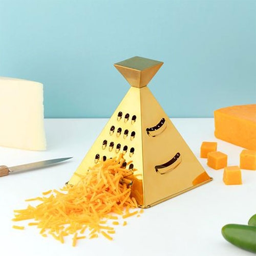 The Nacho Grater by W&P Design is a four-sided, metallic-gold pyramid that offers four grating, shredding and slicing functions.