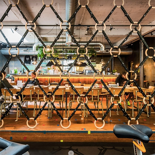 Fascinating use of gymnastic rings to create a room divider between the cafe and workout areas. Tank interior design for de Vondel Gym.