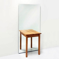 Half a table placed against a mirror changes into a whole table. That is the idea behind Half A Table
