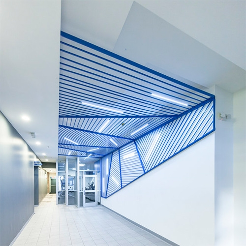 Synecdoche's bright blue Church Street Lobby installation of paneled aluminum bars with LED back lights. This canopy and wall piece is a lighting strategy with minimal intrusion that creates a striking graphic of patterned lines in the central corridor.