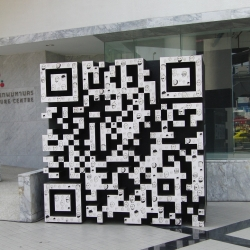 Outside the Modern art and culture museum in Bangkok can you find this piece of art. A QR barcode filled with small faces.