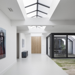 Dutch interior architects i29 transformed a formerly garage space in Amsterdam's area de Pijp into a spacious house naturally lit by large roof lights.
