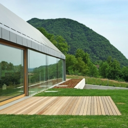 House HB, on top of a low hill, appears to rise from the ground. The roof and side facades are clad in aluminum plates, merging the surfaces, leaving the house with clean lines. By Slovenian Bevk Perović arhitekti.