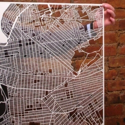 Map of New York City that's literally cut into paper. Manhattan, Brooklyn, Queens and the Bronx fit together like panes of a window, revealing the city's intricacies only when placed against a colorful backdrop. Paris also available.