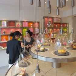 Counterweighted bell jars add to the ultra-modern design aesthetic of La Pâtisserie des Rêves' pastry shop in Paris