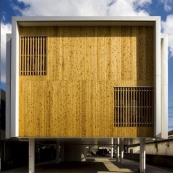 A boxy office building raised on pylons in Oita, Japan.