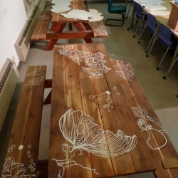 Karyn Fiebich's stenciling design on picnic tables was conceptualized around the environment in which the tables lie and the micro and macro organic components that surround it.