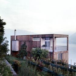A beautiful wooden house, in the middle of a Ticinese vineyard, jutting high above Lake Maggiore in Switzerland. Designed by Daniele Claudio Taddei.