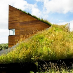 Who needs a balcony when you have a meadow on your roof?! This sloping prefab home definitely gives me green roof envy...