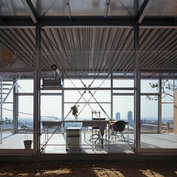 House in Rokko is a minimal home located in Kobe, Japan, designed by Tato Architects. The two-storey steel structure sits atop a flattened slope with a concrete foundation.