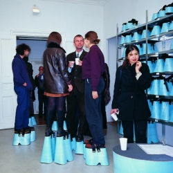 "Berlin-based artist Hans Hemmert  (famous for his work with balloons) threw a party where guests wore shoe-extenders to make them all 2m tall. ""Level"" (1997) was part of the Personal Absurdities show at the Galerie Gebauer Berlin."