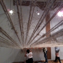 Julia Sherman's A-Room-A-Loom is a site-specific weaving experiment, using the building's walls to turn a room into a simple machine. You're welcome to pitch in and weave your own materials this month! On display at SEA Change in Portland, Oregon.