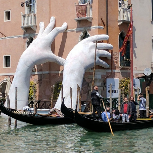 On view until November 26th at the Ca' Sagredo Hotel in Venice during Venice Biennale 2017, Italian artist Lorenzo Quinn's new monumental sculpture features two large hands emerging from the Grand Canal.