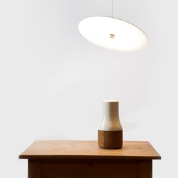 Luna lamp. A hovering brass disk reflects the light which is embedded in the base unit. By Knudsen Berg Hindenes.