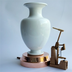 SEVRES VASE CLOCK has an adjustable hammer that gently knocks on any vase you place on the stand on the hour, every hour. Different vases produce different sounds.