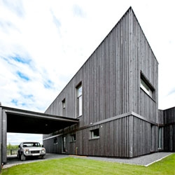 House in Marupe, Latvia by Open AD featuring beautiful metallic grey timber beams.