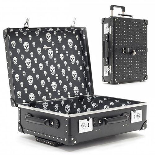 Globe Trotter collaboration with Alexander McQueen. Silver studded black trolley case and and utility case with skull patterned lining and lock of course.