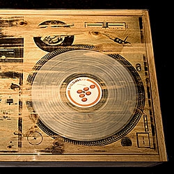 The Scratch DJ Coffee Table by Bughouse doesn't actually play, but you can replace the LP according to your preferences.