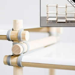 The gummitwist system consists of wooden rods, painted metal shelves and rubber bands.