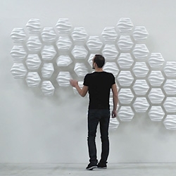 Made of 60 moving modules, HEXI is a responsive wall designed by Thibaut Sld. Its overall shape fluctuates, mirroring our movements.