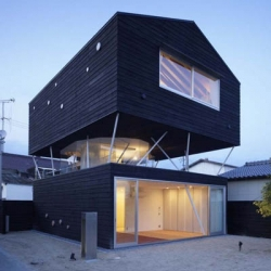 this house, located in Hiroshima, Japan, designed by naf architect & design is developed on 3 levels. The first level is a black cedar box containing the bedroom and the entrance, the second level a terrace whit nothing but steel columns holding up the third level which contains the living room and kitchen.