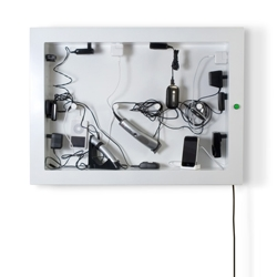 ChargerFrame transforms your electronic landscape into wall art. This active interplay between cables, gadgets and indicator lights is neatly framed and finished off by an energy-efficient master green switch.