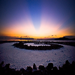 'Sunset at the Spiral Jetty' outlined by rays of sunlight known as crepuscular rays, the setting sun having disappeared from direct view behind them. Seen from the eastern shores of Great Salt Lake, Utah.
