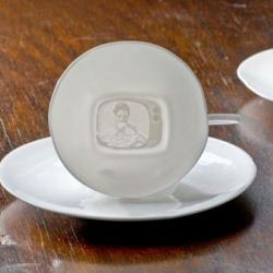Tea V is a tea cup handmade by Jana Wallser out of porcelain. If you come closer and lift the cup and light shines through the bottom, you can see a picture of a woman in a television, who is drinking tea.