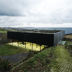 OS house. Located in Cantabria, Spain, this house builds an inner yard to get an open space protected from winds, while taking advantage of solar gain and cross ventilation and integrating with the landscape through a green roof. By Nolaster Arquitectos.
