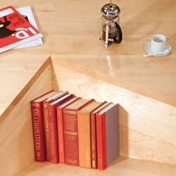 Nook by Dave Pickett is a coffee table with an integrated bookshelf that acts as the '4th' leg to balance your heavy volumes of antiquity.