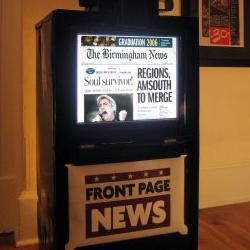 "Newspaper machine with an lcd monitor shows a newspaper slideshow.  A news ""jukebox""?  
