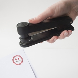 'Stampler' designed by Phil Jones in partnership with Suck UK. It looks and works like a normal stapler – but has an added attachment that prints a smiling face design at the same time.