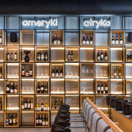 In Poland a new culinary scene has arisen. Since a chef rules the roost during shows, the architect has proposed an exposed kitchen, which is like a scene. Neon signs above the shelvings make it easier to find a bottle from one's own favourite place in the world.