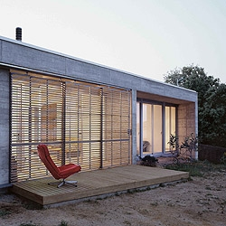 A compact concrete house. Its shape is determined by the plot restrictions. Features an inner patio for cross ventilation and natural lighting.  By H Arquitectes in Catalunya, Spain.