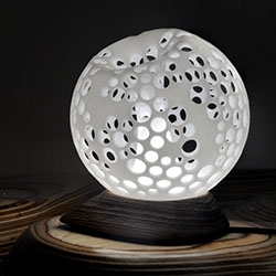 Celestial - An orb shaped desk lamp where the perforated outer shell of the shade folds back into the center to form a stem, gently diffusing light. By Artonomos.