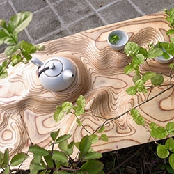 Tea Tray carved out of plywood. Undulating forms accentuated by the layers of the ply, and a large central reservoir is formed by the landscape where excess tea gathers to form a lake. By Artonomos.