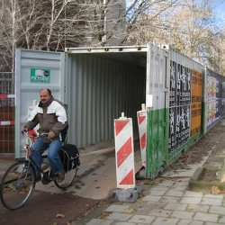 The Netherlands have the most dense bike lane network in the world. Next to a building site a contractor placed a row of containers to keep the Dutch bikers going.