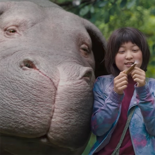 "The trailers for Okja are so fun. ""Tilda Swinton, Jake Gyllenhaal and Paul Dano star in this drama about a girl who must keep a powerful company from abducting her pal, a gentle beast."""