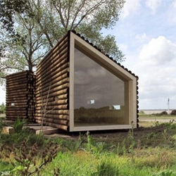 A small cabin in Nantes, designed by french architects OLGGA. The exterior is cladded with logs, looking like a pile of wood in the middle of the nature.