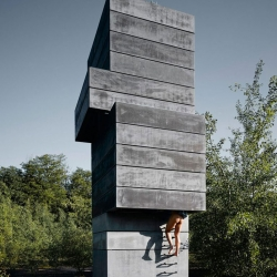 The One Man Sauna stands on an abandoned factory site in Bochum, Germany. A stacked tower of concrete shaft mine components containing a plunge pool, a sauna, and a meditation room with a skylight.