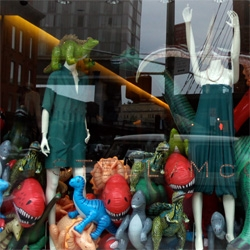 Stella McCartney's store in NY has a window filled with inflatable dinosaurs... and headless mannequins with their arms up in fear!