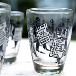 A close up look at a vintage glassware set featuring classic cocktail recipes and playful illustrations!