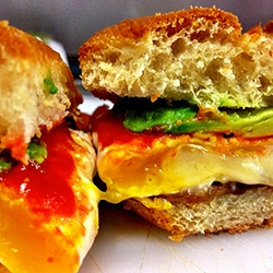 How to Make The Ultimate Egg Sandwich over at the freshly opened Summers Juice and Coffee in Brooklyn. Between the special bun is a spiral of sriracha, avocado, bacon, and a fried egg filled with cheese.